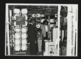 A man, woman and two children tour textile mill