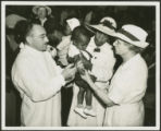African-American child receiving typhoid vaccine from county health doctor and W.P.A. nurse